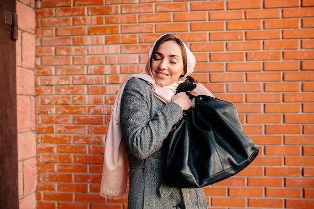 Giovane bella donna felice molto soddisfatta di una nuova borsa