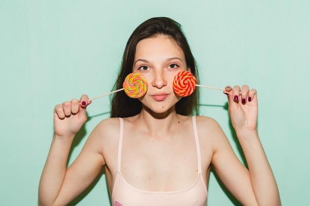 Giovane bella donna hipster in posa contro il muro blu, con in mano caramelle pop lecca-lecca
