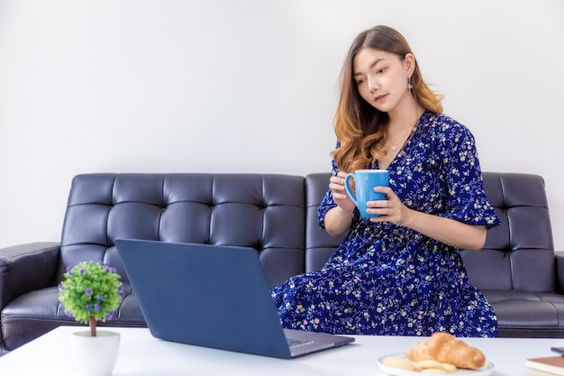 Giovane bella donna in abito blu che lavora al suo computer nel suo salotto di casa