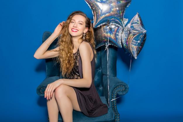 Giovane bella donna in abito grigio seduto su una poltrona blu con palloncini d'argento