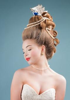 Giovane bella donna in abito vittoriano vintage con acconciatura complicata