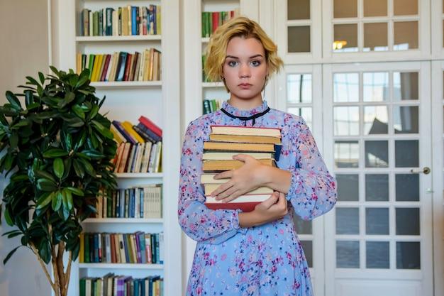 Giovane bella donna in biblioteca con i libri
