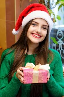 Giovane bella donna in cappello di babbo natale rosso tenendo il contenitore di regalo