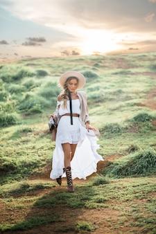 Giovane bella donna in cappello e vestito bianco lungo sulla natura. boho, hipster, concetto di moda