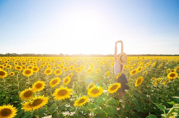 Giovane bella donna in cappello in piedi all'aperto sulla luminosa mattina d'estate in girasole f