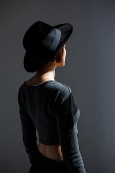 Giovane bella donna in cappello nero che sta di nuovo alla macchina fotografica