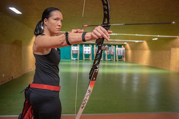 Giovane bella donna in competizioni sportive, tiro con l'arco, mirando al bersaglio