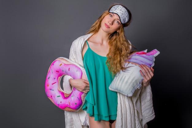 Giovane bella donna in indumenti da notte con cuscini divertenti