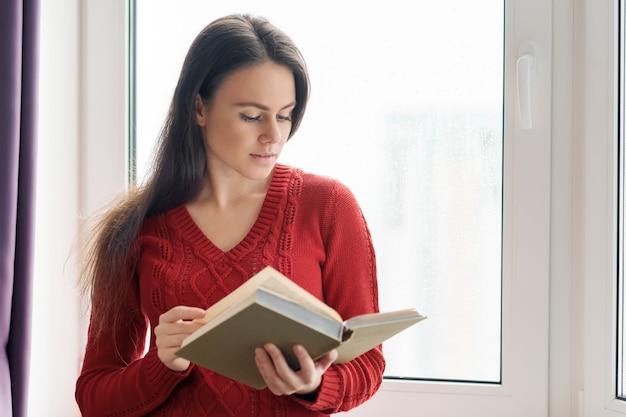 Giovane bella donna in libro di lettura rosso del maglione