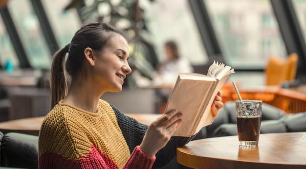 Giovane bella donna in maglione arancione che legge libro interessante in caffè