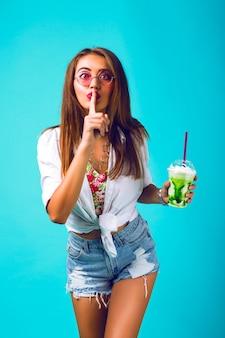 Giovane bella donna in mini shorts in denim che beve gustoso frullato, vestito vintage, make up occhiali da sole