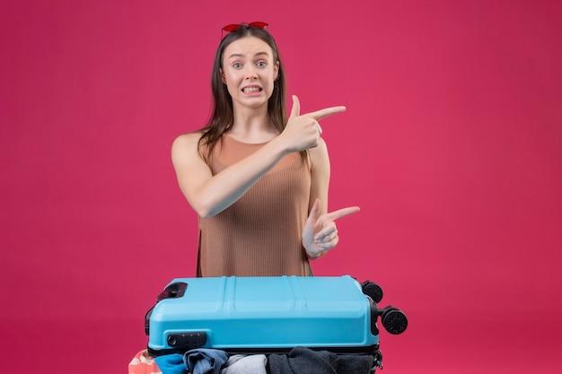 Giovane bella donna in piedi con la valigia da viaggio che punta con le dita a lato cercando confuso su sfondo rosa