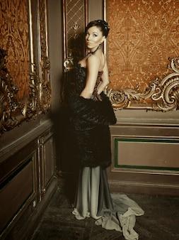 Giovane bella donna in piedi nella stanza del palazzo