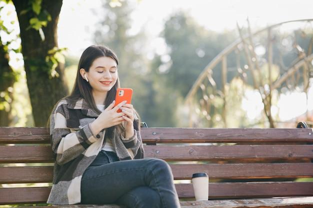 Giovane bella donna in piedi su una panchina utilizzando il computer portatile