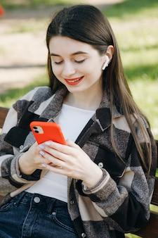 Giovane bella donna in piedi su una panchina utilizzando il telefono