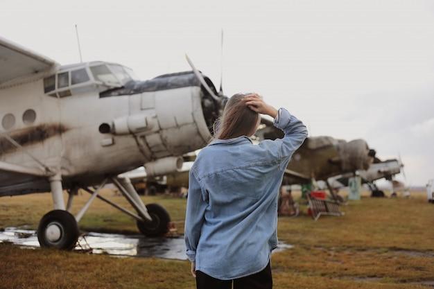 Giovane bella donna in piedi vicino all'aereo. viaggiare e tecnologia. vista posteriore