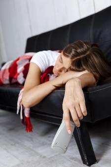 Giovane bella donna in plaid che dorme sul divano di casa.