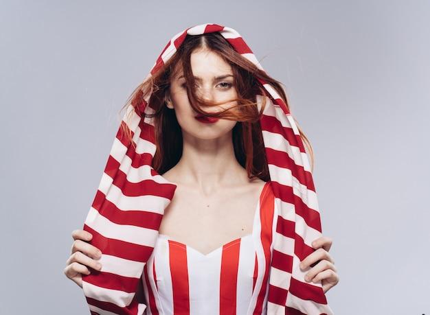 Giovane bella donna in studio, tessuto a strisce di colore rosso sulla testa e vestito alla moda