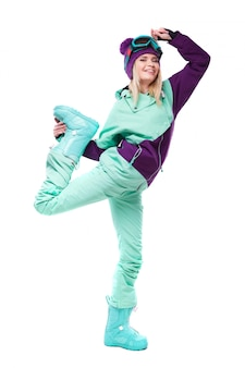 Giovane bella donna in tuta da sci viola e stivali da neve blu