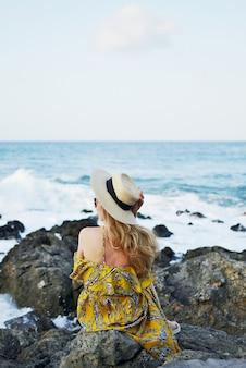 Giovane bella donna in un cappello e maxi vestito, giornata di sole, vacanze, natura tropicale, grecia, isola di creta