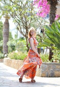 Giovane bella donna in un cappello e un maxi vestito giallo, giorno soleggiato, concetto di libertà, vacanza, natura tropicale