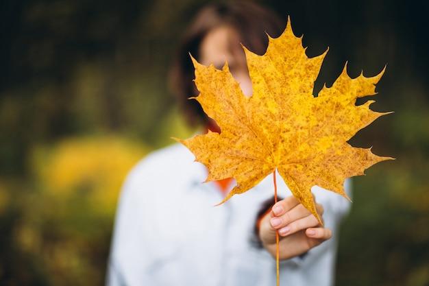 Giovane bella donna in un parco in autunno pieno di foglie