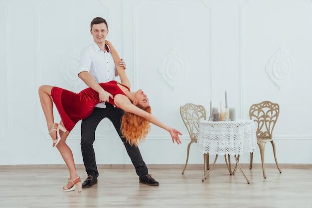 Giovane bella donna in un vestito rosso e un uomo che balla isolato su uno sfondo bianco.