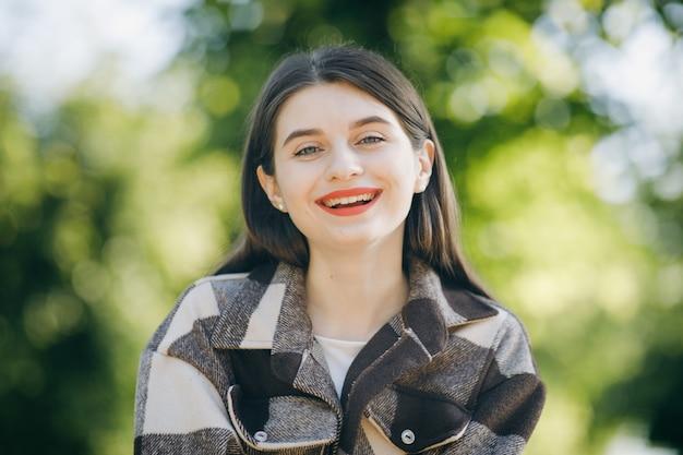 Giovane bella donna in una camicia nel parco