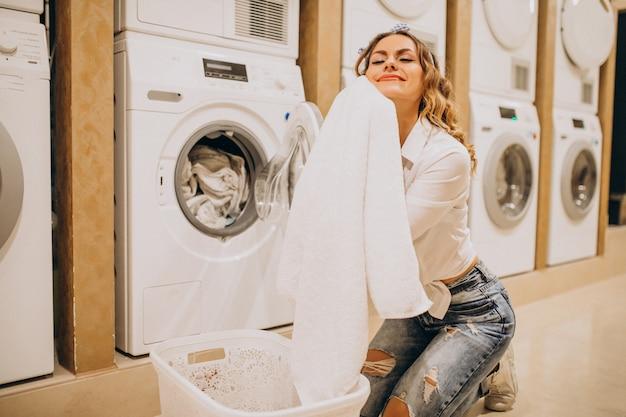 Giovane bella donna in una lavanderia a gettoni