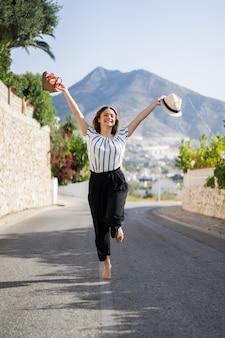 Giovane bella donna in vacanza saltando. in una mano sandali nel cappello di seconda mano.