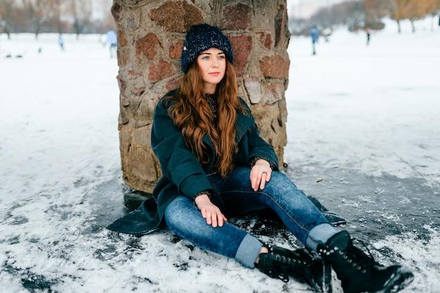 Giovane bella donna in vestiti alla moda con capelli marroni lunghi che si siedono sotto il ponte sul ghiaccio sul lago congelato nel giorno di inverno freddo del gelo