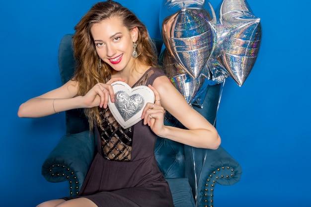 Giovane bella donna in vestito grigio che si siede su una poltrona blu che tiene cuore d'argento