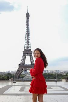 Giovane bella donna in vestito rosso che sta davanti alla torre eiffel a parigi
