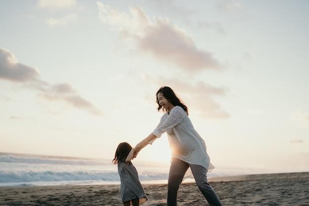 Giovane bella donna incinta con la sua piccola figlia carina giocando in spiaggia