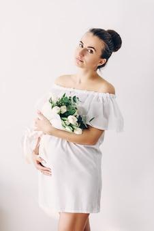 Giovane bella donna incinta in un abito bianco con un mazzo di tulipani bianchi