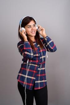 Giovane bella donna indiana che ascolta la musica contro la parete grigia