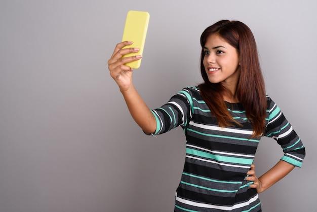 Giovane bella donna indiana che per mezzo del telefono cellulare contro la parete grigia