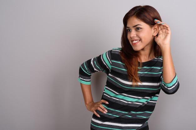 Giovane bella donna indiana contro la parete grigia