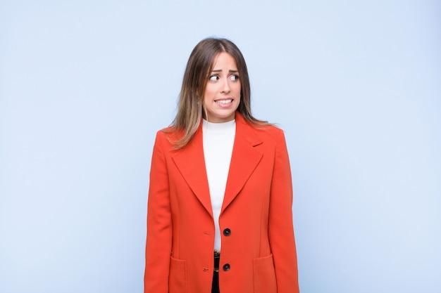 Giovane bella donna ispanica che sembra preoccupata, stressata, ansiosa e spaventata, in preda al panico e stringe i denti contro il muro blu