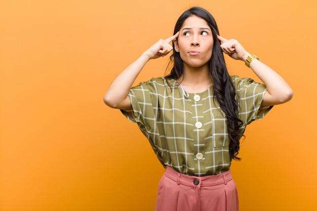 Giovane bella donna ispanica sentirsi confusa o in dubbio, concentrandosi su un'idea, pensando intensamente, cercando di copiare lo spazio sul lato contro il muro marrone