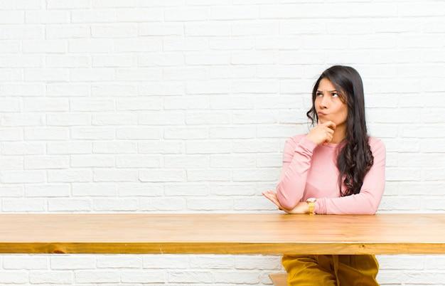 Giovane bella donna latina che pensa, si sente dubbiosa e confusa, con diverse opzioni, chiedendosi quale decisione prendere prendendo davanti a un tavolo