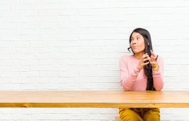 Giovane bella donna latina che si sente orgogliosa, birichina e arrogante mentre progetta un malvagio pensiero di un trucco seduto di fronte a un tavolo