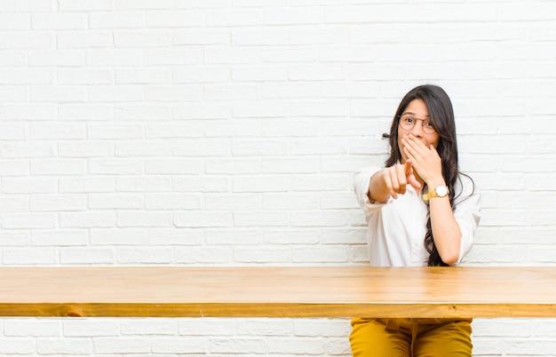 Giovane bella donna latina che ti ride, indicando e prendendo in giro o deridendoti seduto di fronte a un tavolo