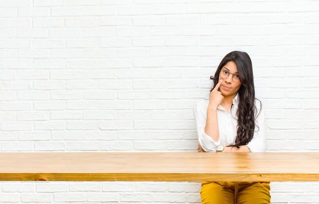 Giovane bella donna latina che ti tiene d'occhio, non fidandoti, guardando e rimanendo vigile e vigile seduto di fronte a un tavolo