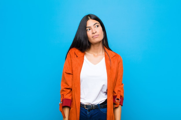 Giovane bella donna latina con un'espressione preoccupata, confusa, all'oscuro, alzando lo sguardo per copiare lo spazio, dubitando contro la parete piatta