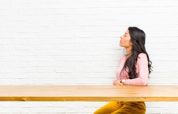 Giovane bella donna latina sentirsi confusa o piena o dubbi e domande, chiedendosi, con le mani sui fianchi, vista posteriore seduto davanti a un tavolo