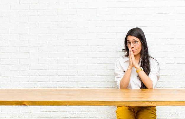 Giovane bella donna latina sentirsi preoccupata, piena di speranza e religiosa, pregando fedelmente con i palmi premuti, chiedendo perdono seduto di fronte a un tavolo