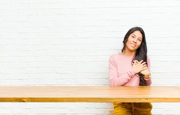 Giovane bella donna latina sentirsi romantica, felice e innamorata, sorridendo allegramente e tenendosi per mano vicino al cuore, seduta di fronte a un tavolo