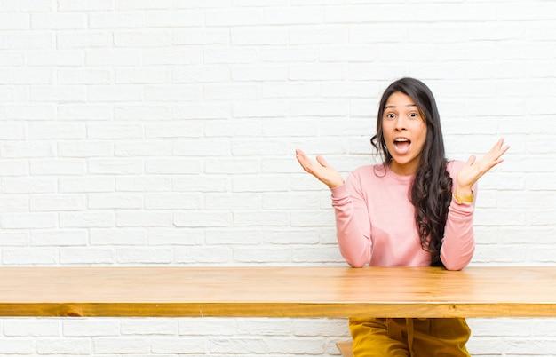 Giovane bella donna latina sentirsi scioccata ed eccitata, ridendo, stupita e felice a causa di una sorpresa inaspettata seduta di fronte a un tavolo