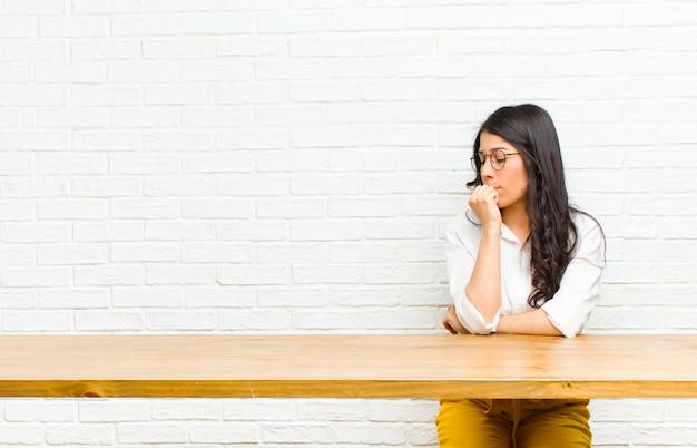 Giovane bella donna latina sentirsi seria, riflessiva e preoccupata, fissando lateralmente con la mano premuta contro il mento seduto davanti a un tavolo